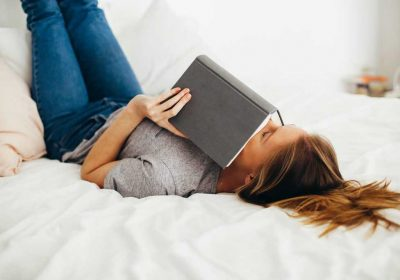 woman-lying-on-bed-holding-book-1458669